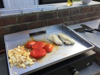 Grilling fish with tomatoes and onions from the garden